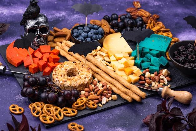Assiette de fromages avec de la nourriture d'halloween aux raisins
