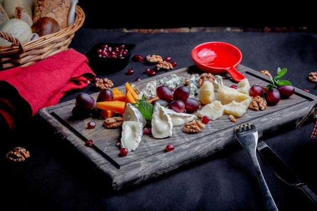 Assiette de fromages servi avec des raisins et des noix sur un fond en bois