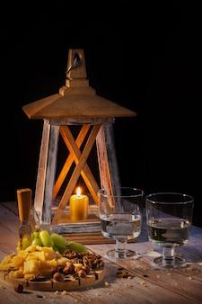Assiette de fromages avec une variété de collations sur la table avec deux verres de vin aux chandelles