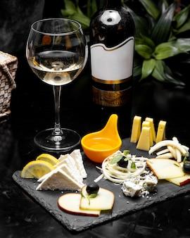 Assiette de fromages avec vue de côté de vin blanc