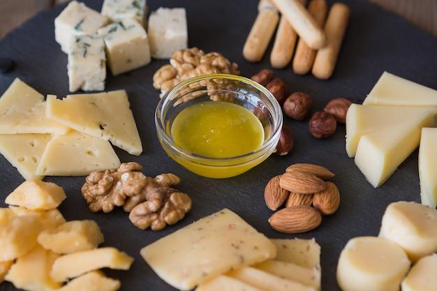 Assiette de fromages vue de dessus assortiment de différents types de fromages sur planche à découper en ardoise foncée