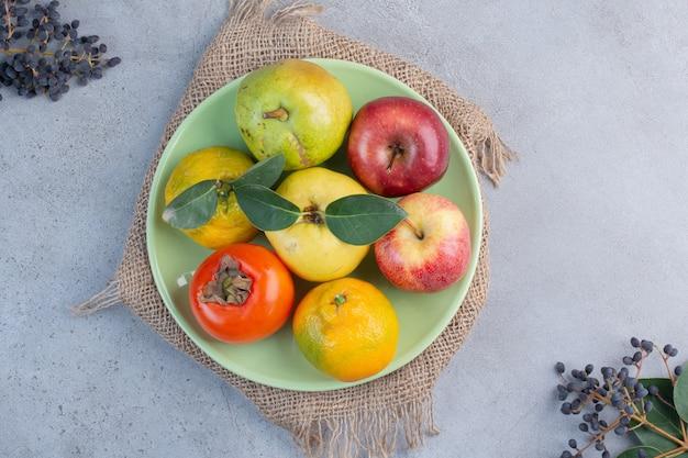 Assiette de fruits assortis sur un morceau de tissu sur fond de marbre.