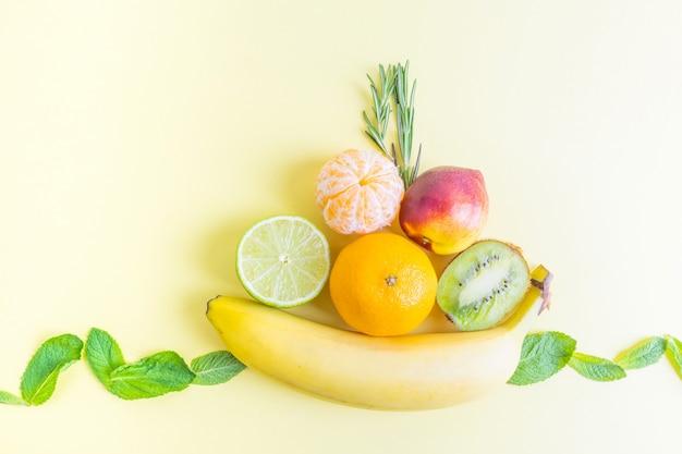 Assiette de fruits - banane, kiwi, mandarine, nectarine, citron vert - sur un jaune pastel.