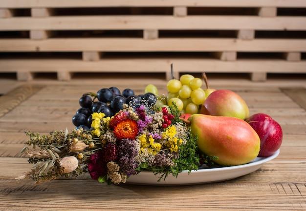 Assiette de fruits avec des décorations de fleurs sauvages sur la table en bois