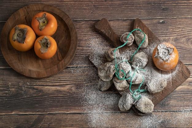 Assiette de fruits frais fuyu et kaki séchés sur planche de bois