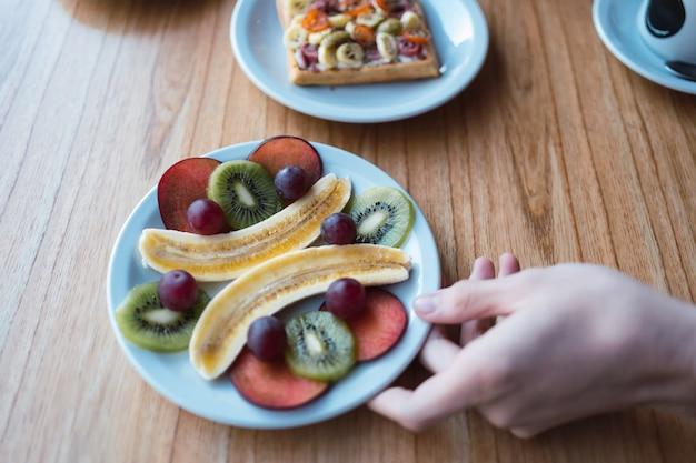 Assiette de fruits frais sur une table en bois - petit-déjeuner sain ou dessert avec prunes, raisins, bananes et kiwi.