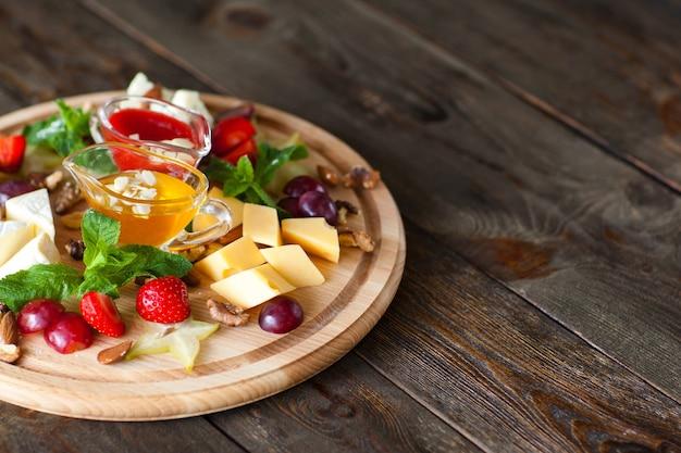 Assiette de fruits et de fromages sur un bureau en bois