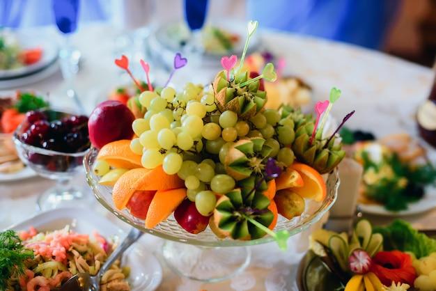 Assiette de fruits avec orange fraîche, raisins, kiwi et pomme