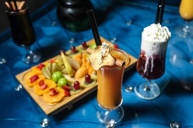 Assiette de fruits orange fraise kiwi poire jus de pêche milkshake vue latérale