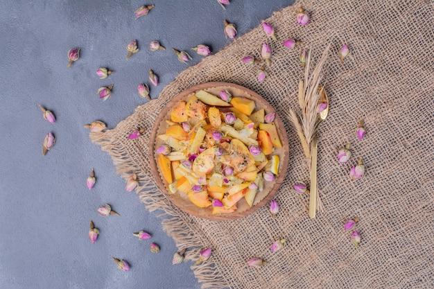 Assiette de fruits en tranches avec des fleurs et un chiffon sur fond bleu.