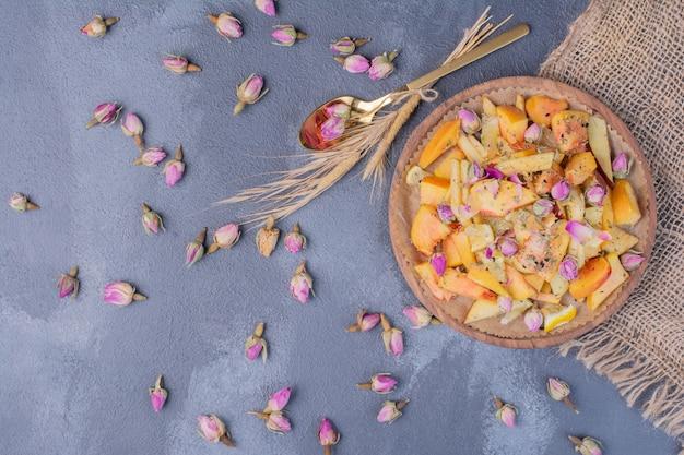 Assiette de fruits en tranches avec des fleurs sur fond bleu.