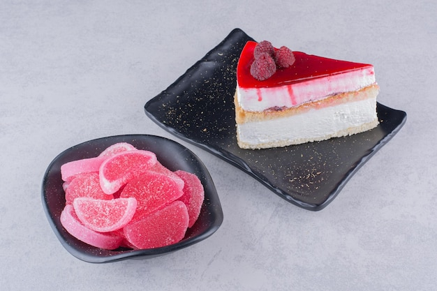 Assiette de gâteau au fromage et bol de bonbons sur une surface en marbre.