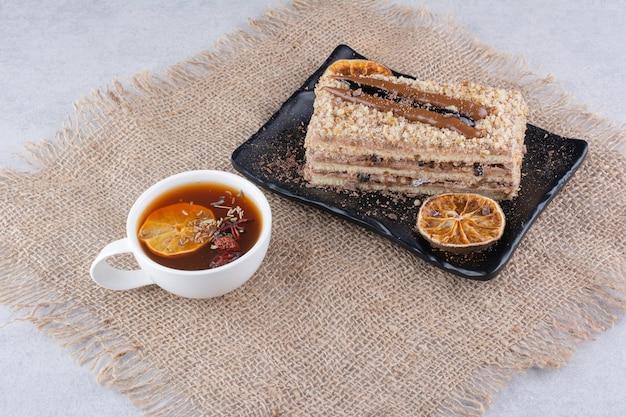 Assiette de gâteau fait maison avec thé aux fruits sur toile de jute. photo de haute qualité