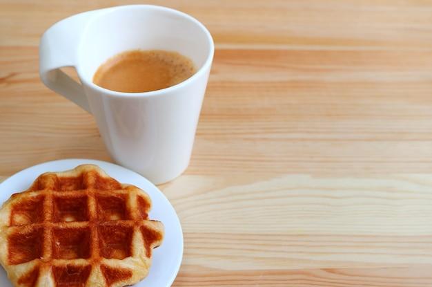 Assiette d'une gaufre de liège avec du café chaud flou en arrière-plan