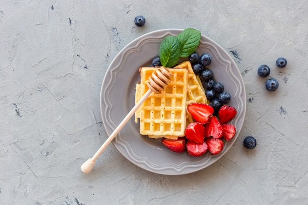 Assiette de gaufres décorées de miel et de baies fraîches sur une surface en pierre grise. concept alimentaire. vue de dessus.