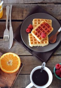 Assiette de gaufres à la marmelade de framboises, jus d'orange et café