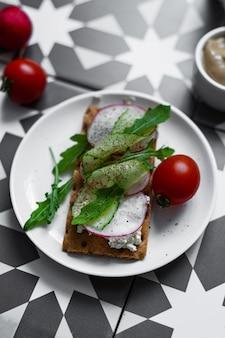 Une assiette grise avec un sandwich au buko, radis et oruguts sur une table graphique colorée (style asiatique, sudiste). un petit-déjeuner sain avec des légumes et des herbes. bonne collation