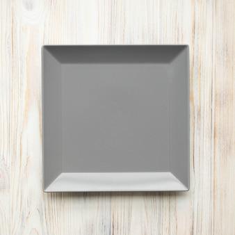 Assiette grise vide sur une table en bois blanc, vue de dessus, photo carrée