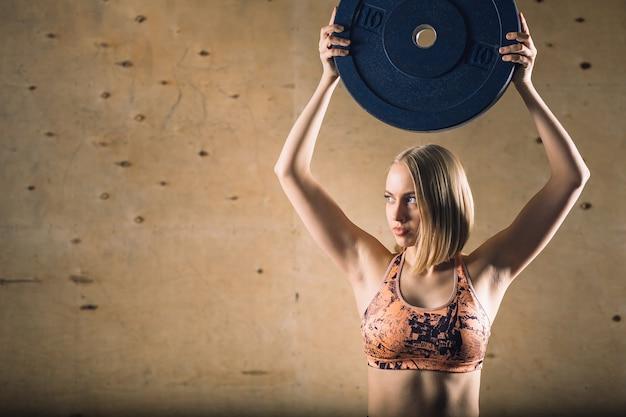 Assiette haltère augmenter l'entraînement de fille blonde à l'exercice de gym