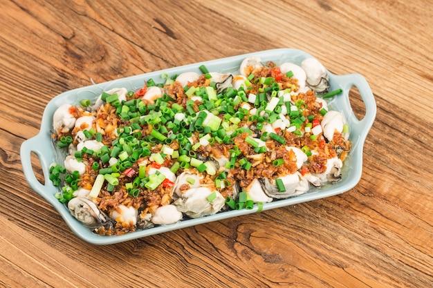 Une assiette d'huîtres fraîches cuites à la vapeur avec des vermicelles