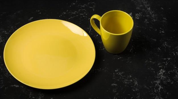 Une assiette jaune vide et une tasse de thé sur un fond texturé noir avec une copie de l'espace.