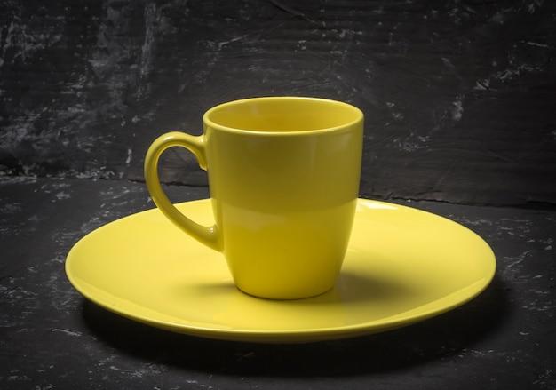 Assiette jaune vide et tasse de thé sur fond texturé noir.