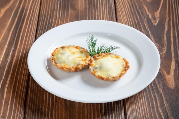 Assiette de julienne avec fromage et champignons sur une table en bois