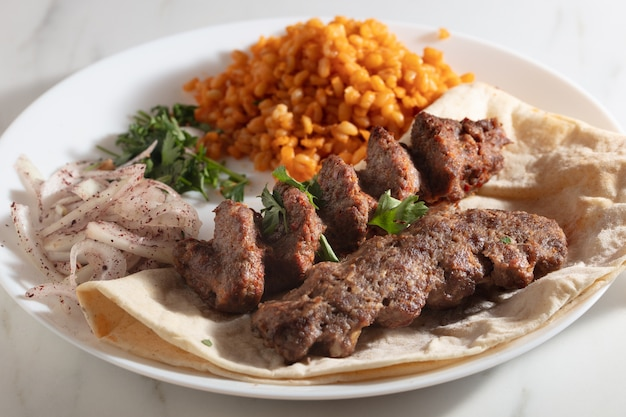 Assiette de kebab avec du pain et des oignons et du riz épicé