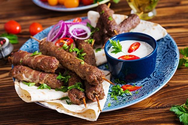 Assiette de kebab de mélange de ramadan traditionnel turc et arabe. kebab adana, poulet, agneau et boeuf sur pain lavash avec sauce. vue de dessus