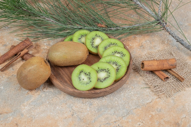Assiette de kiwi frais et bâtons de cannelle sur fond de marbre. photo de haute qualité