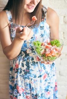 Assiette avec des légumes frais dans les mains de la femme enceinte