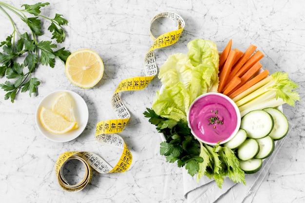 Assiette de légumes avec ruban à mesurer et sauce rose