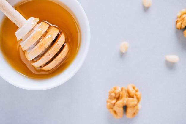 Assiette avec une louche de miel, noix et pignons sur un fond blanc, vue de dessus