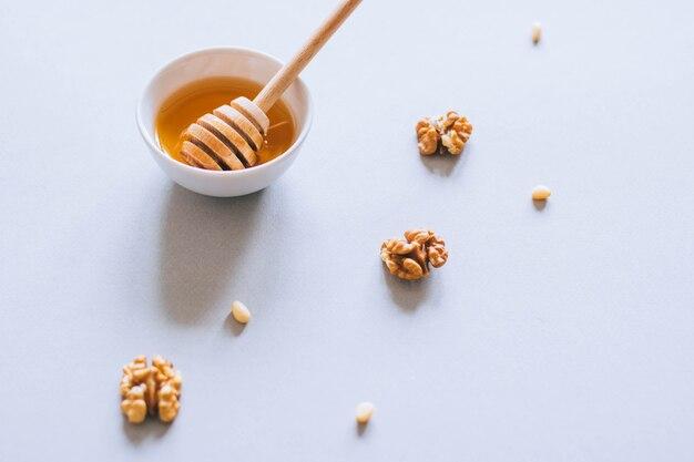 Assiette avec une louche de miel, noix et pignons sur un fond blanc