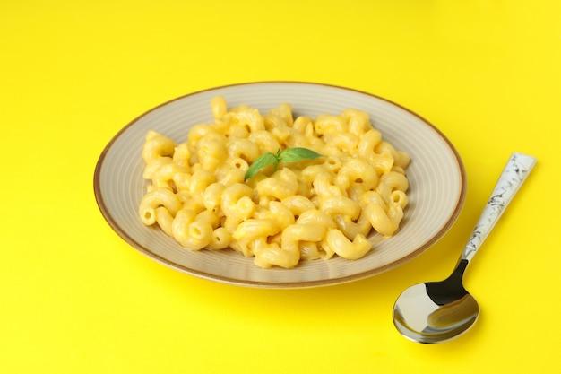 Assiette de macaronis au fromage sur fond jaune