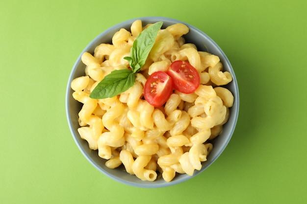 Assiette de macaronis au fromage sur fond vert