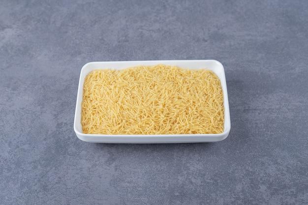 Assiette de macaronis crus sur fond de pierre.