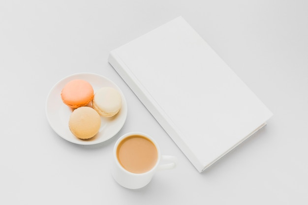 Assiette avec macarons à côté de livre sur table