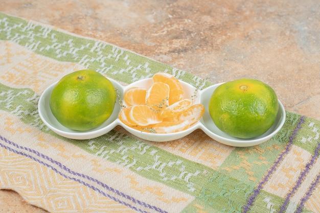 Assiette de mandarines fraîches et segments sur nappe.