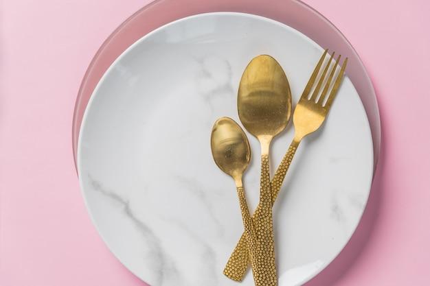 Assiette en marbre, couteau en or, fourchette et cuillère sur le mur rose. vaisselle et couverts, assiette avec cuillères et fourchette. dîner, nourriture d'amour romantique et concept de cuisine d'amour.