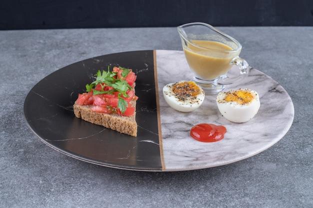 Une assiette en marbre avec œuf à la coque et pain grillé. photo de haute qualité
