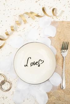 Assiette de mariage vue de dessus avec pétales