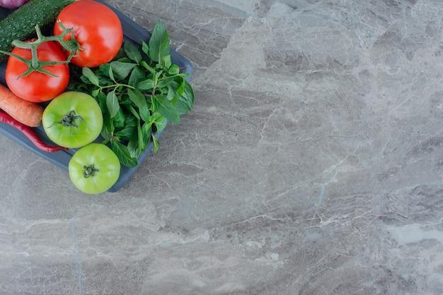 Assiette marine garnie de concombre, carotte, tomates rouges et vertes, navet blanc, poivrons verts et rouges, oignons rouges et menthe sur marbre