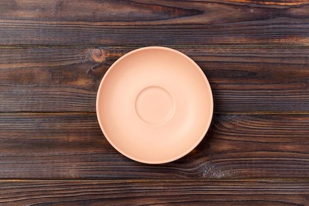 Assiette mat orange vide sur fond en bois