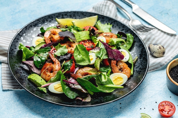 Assiette avec un menu diététique céto avec tomates cerises, concombre, avocat, œufs et crevettes fumées, mesclun. la nourriture saine. manger propre.