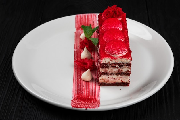 Assiette avec morceau de délicieux gâteau de velours rouge sur fond de bois noir concept de nourriture et de boisson