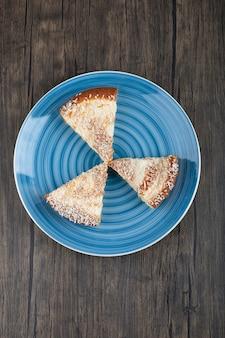 Assiette avec des morceaux de tarte aux pommes maison savoureuse sur bois.