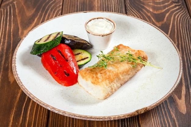 Assiette de morue grillée avec légumes et sauce blanche sur table en bois