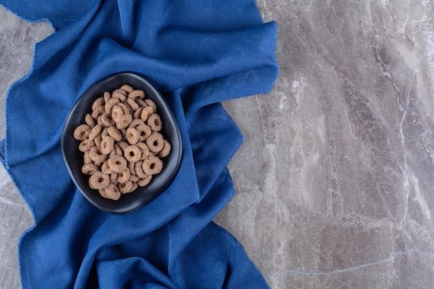 Une assiette noire d'anneaux de céréales au chocolat sain pour le petit-déjeuner.