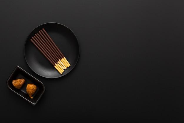 Assiette noire avec des bâtons de chocolat sur un fond sombre